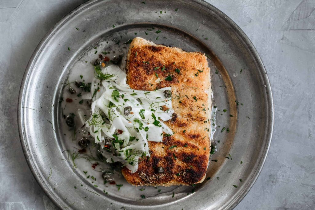 While almond crusted fish piccata may bear little resemblance to the red-and-white checkered classic, it's fresher, nuttier & keeps all the familiar flavors.